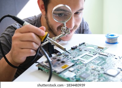 Young adult repairing a printed circuit board with a soldering iron through a magnifying glass. Technology concept.