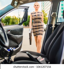 young adult sexy business lady going out to car with opening door. Empty auto interior inside. Stylish Businesswoman wear short dress with suit case. front view woman.  shot through interior of  car.