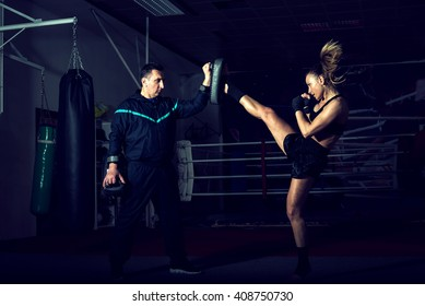 Young adult sexy woman doing back leg high kick during kickboxing exercise with trainer