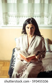Young adult sexy woman reading a book in apartment
