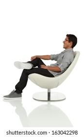 young adult sitting and leaning back on modern chair side view