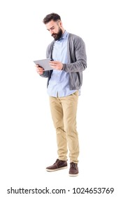 Young adult smart casual businessman holding and watching tablet computer. Full body length portrait isolated on white studio background.