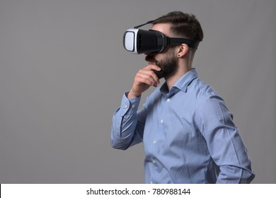 Young Adult Smart Casual Businessman Wearing Head Mounted Vr Headset  Looking Away At Copyspace And Thinking