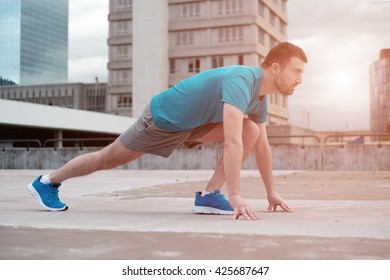 young adult sportsman working out in the city