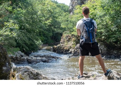 young adult standing at river enjoying the view after his hiking activity