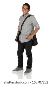 Young adult standing with a shoulder bag holding a laptop.