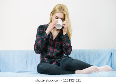 Young adult or teenage woman enjoying her leisure time drinking coffee or tea from mug.