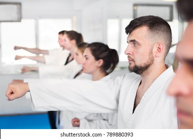 Young adult trainees practicing of new maneuvers at karate class