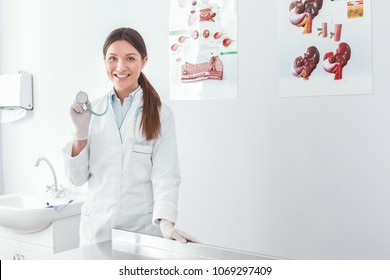Young adult vet woman holding a stethoscope and toothy smiling at camera. Veterinary clinic concept. Services of a doctor for animals, health and treatment of pets