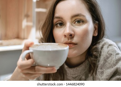 Young adult white woman with big cup of latte, selective focus