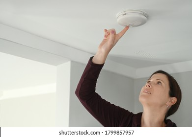 Young adult woman (age 25-35) checking fire alarm at home.