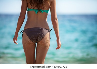 Young adult woman in bikini standing on the beach. Photography shows her buttocks on which are the grains of sand.