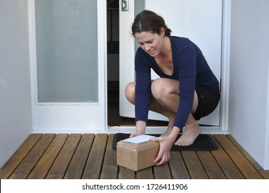 Young adult woman collecting a package postal box courier delivery from home doorstep front porch.