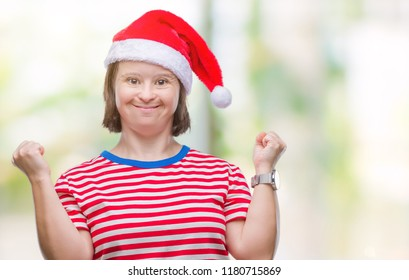 Young adult woman with down syndrome wearing christmas hat over isolated background celebrating surprised and amazed for success with arms raised and open eyes. Winner concept.