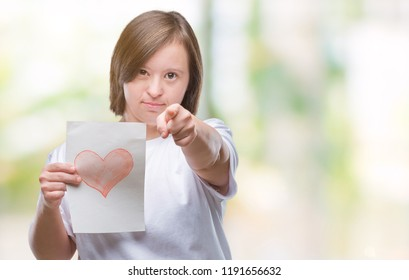 Young adult woman with down syndrome holding red heart card over isolated background pointing with finger to the camera and to you, hand sign, positive and confident gesture from the front