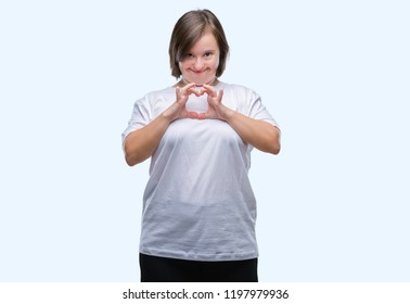 Young adult woman with down syndrome over isolated background smiling in love showing heart symbol and shape with hands. Romantic concept.