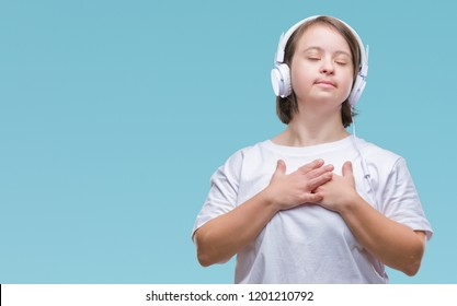 Young adult woman with down syndrome wearing headphones over isolated background smiling with hands on chest with closed eyes and grateful gesture on face. Health concept.