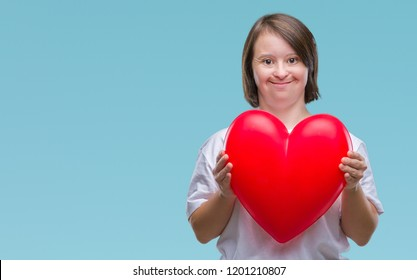 Young adult woman with down syndrome holding red heart over isolated background with a happy face standing and smiling with a confident smile showing teeth