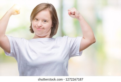 Young adult woman with down syndrome over isolated background showing arms muscles smiling proud. Fitness concept.