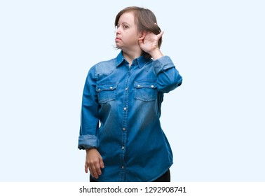 Young adult woman with down syndrome over isolated background smiling with hand over ear listening an hearing to rumor or gossip. Deafness concept.
