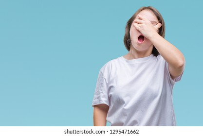 Young adult woman with down syndrome over isolated background peeking in shock covering face and eyes with hand, looking through fingers with embarrassed expression.