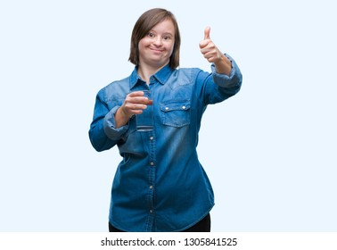 Young adult woman with down syndrome drinking water over isolated background happy with big smile doing ok sign, thumb up with fingers, excellent sign