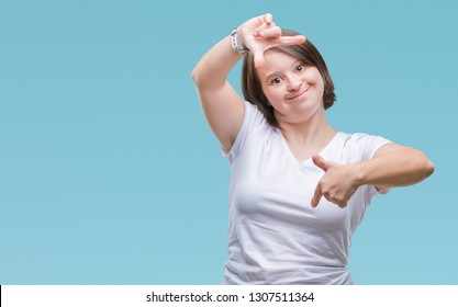Young adult woman with down syndrome over isolated background smiling making frame with hands and fingers with happy face. Creativity and photography concept.