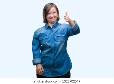 Young adult woman with down syndrome over isolated background doing happy thumbs up gesture with hand. Approving expression looking at the camera with showing success.