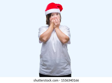 Young adult woman with down syndrome wearing christmas hat over isolated background shocked covering mouth with hands for mistake. Secret concept.