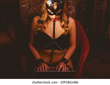 Young adult woman dressed in leather black mask, underwear and sword belt sitting in armchair and using laptop.