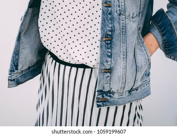 Young adult woman dressed white t-shirt with black peas pattern, striped skirt and denim jacket.