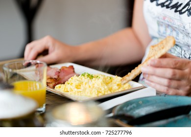 Young adult woman eats delicious scrambed eggs with juicy bacon. Close up shot with focus on scrumbled eggs on plate