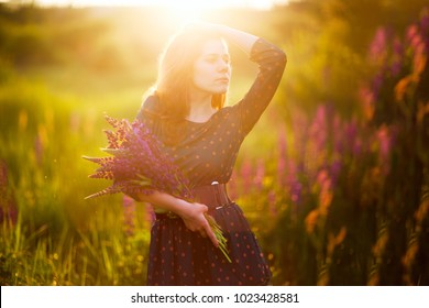 Young adult woman in green dress with bouquet of lupines in hands against a background of flowering meadow. Sunlight on the face. Spring, Summer. Beautiful morning, evening lighting.