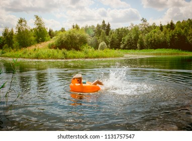 Young adult woman having fun, resting and sunbathing, relaxing on inflatable round orange chair toy and floating on lake pond in nature outdoors in summer.