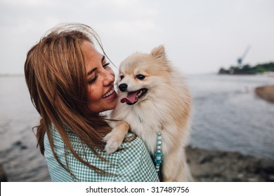 Young adult  woman is holding a dog on her shoulder. Woman turned back around.