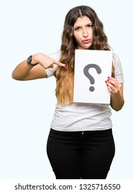 Young adult woman holding paper with question mark with surprise face pointing finger to himself
