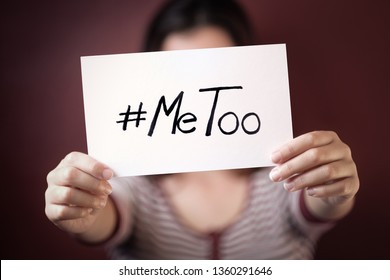 Young adult woman holding a sign with the hashtag MeToo