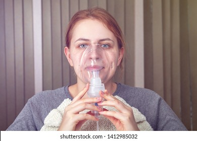 Young adult woman with idiopathic pulmonary fibrosis is doing inhalation with nebulizer mask.