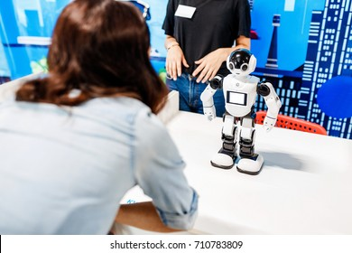 Young adult woman looking at the toy robot at the exhibition