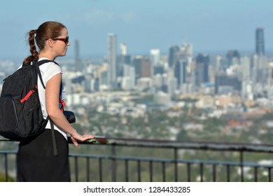 Young adult woman looking at urban city skyline on her city break travel holiday vacation.