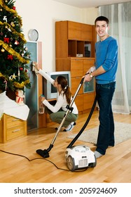 Young adult woman and man doing housework together in home