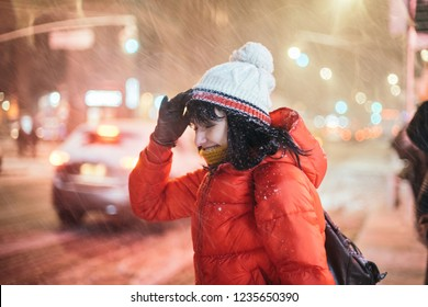 Young adult woman on city street uder winter snow storm at night time.