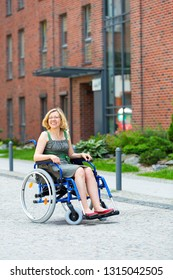 young adult woman on wheelchair on the street smiling and looking somewhere