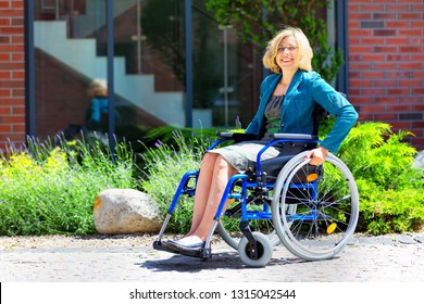 young adult woman on wheelchair on the street smiling and looking straight to the camera