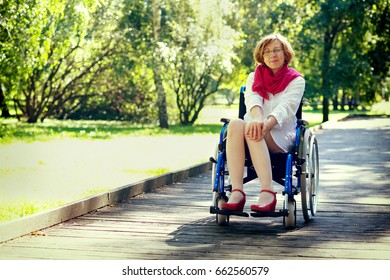 young adult woman on wheelchair in the park looking straight to the camera