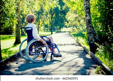 young adult woman on wheelchair in the park, side view
