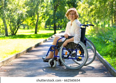 young adult woman on wheelchair in the park looking straight to the camera and smiling