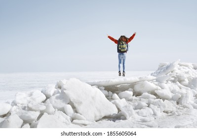 Young adult woman outdoors travelling with backpack in icy landscape