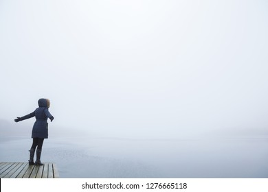 Young adult woman with outstretched arms standing on footbridge. Staring at lake. Mist over water. Foggy air. Peaceful atmosphere. Side view. Empty place for text, quote or sayings on sky background.