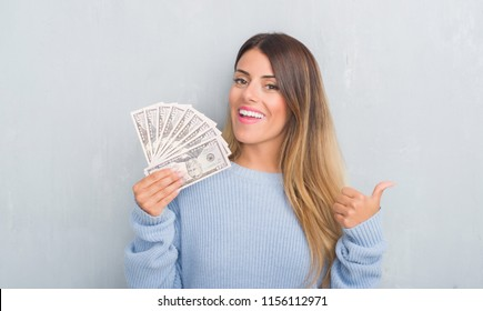 Young adult woman over grey grunge wall holding dollars pointing and showing with thumb up to the side with happy face smiling